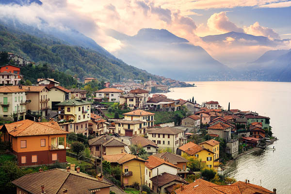 Cmall town on the slopes of Alps mountain on Como Lake, Milan, Italy, on sunset
